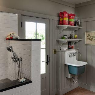 Inspiration pour une buanderie rustique avec un évier utilitaire, un mur gris, un sol en bois brun, un sol marron et du lambris.