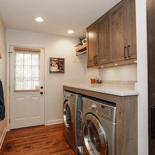 Bild på en liten rustik linjär tvättstuga enbart för tvätt, med luckor med infälld panel, skåp i mellenmörkt trä, marmorbänkskiva, vita väggar, mellanmörkt trägolv och en tvättmaskin och torktumlare bredvid varandra