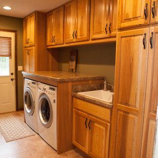 Exempel på en mellanstor klassisk linjär tvättstuga, med en undermonterad diskho, luckor med upphöjd panel, granitbänkskiva, beige stänkskydd, stänkskydd i stenkakel, ljust trägolv och skåp i mellenmörkt trä