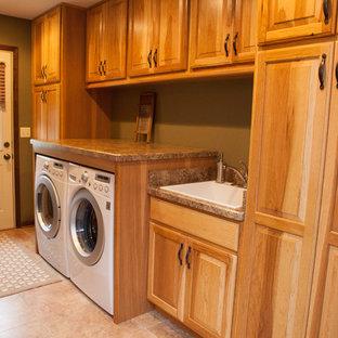 Exempel på en mellanstor klassisk u-formad tvättstuga, med en undermonterad diskho, luckor med upphöjd panel, granitbänkskiva, beige stänkskydd, stänkskydd i stenkakel, ljust trägolv och skåp i mellenmörkt trä