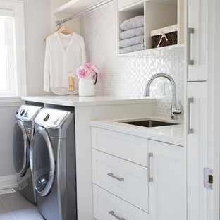 Immagine di una sala lavanderia chic con lavello sottopiano, ante in stile shaker, ante bianche, pareti grigie, lavatrice e asciugatrice affiancate, pavimento grigio e top bianco