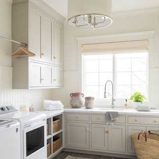 Design ideas for a large coastal l-shaped separated utility room in Salt Lake City with grey cabinets, marble worktops, white walls, ceramic flooring, a side by side washer and dryer, grey floors and multicoloured worktops.