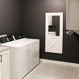 Bild på en mellanstor vintage grå parallell grått tvättstuga enbart för tvätt, med skåp i shakerstil, vita skåp, svarta väggar, en tvättmaskin och torktumlare bredvid varandra och grått golv
