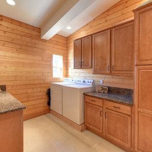 Idéer för mycket stora lantliga tvättstugor, med luckor med upphöjd panel, skåp i mellenmörkt trä, granitbänkskiva, bruna väggar, betonggolv, en tvättmaskin och torktumlare bredvid varandra och beiget golv