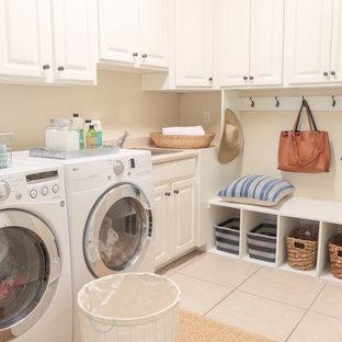 Foto på ett litet vintage l-format grovkök, med en nedsänkt diskho, luckor med upphöjd panel, vita skåp, laminatbänkskiva, beige väggar, klinkergolv i keramik, en tvättmaskin och torktumlare bredvid varandra och beiget golv