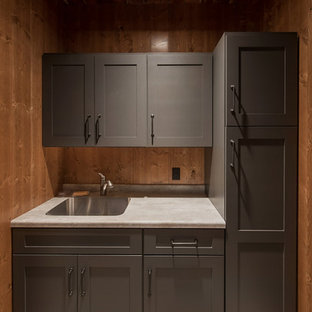 Foto di una lavanderia rustica di medie dimensioni con lavello a vasca singola, ante lisce, ante grigie, top in laminato e paraspruzzi in legno