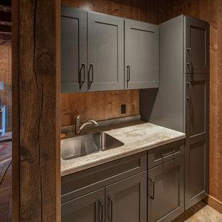 Inspiration pour une buanderie linéaire chalet de taille moyenne avec un évier 1 bac, un placard à porte plane, des portes de placard grises, un plan de travail en stratifié et une crédence en bois.
