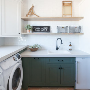 Large country galley dedicated laundry room in Phoenix with a drop-in sink, shaker cabinets, green cabinets, white walls, terra-cotta floors, a side-by-side washer and dryer, orange floor, grey benchtop and concrete benchtops.