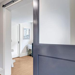 Exempel på ett mellanstort amerikanskt vit linjärt vitt grovkök, med en allbänk, släta luckor, blå skåp, bänkskiva i kvarts, grå väggar, en tvättmaskin och torktumlare bredvid varandra, brunt golv och bambugolv