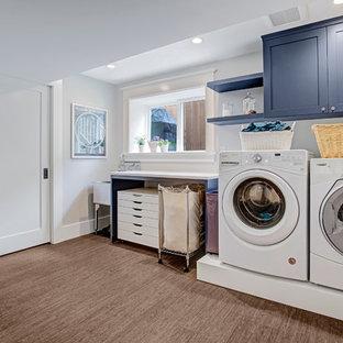 Immagine di una lavanderia multiuso american style di medie dimensioni con lavatoio, ante lisce, ante blu, top in quarzo composito, pareti grigie, lavatrice e asciugatrice affiancate, pavimento marrone, top bianco e pavimento in bambù