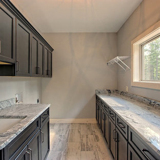 Example of a large arts and crafts galley ceramic floor and gray floor utility room design in Atlanta with an undermount sink, recessed-panel cabinets, black cabinets, granite countertops, gray walls and gray countertops