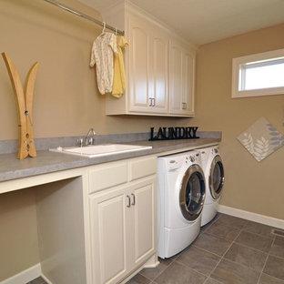 Idee per una sala lavanderia stile americano con lavello da incasso, ante con bugna sagomata, ante beige, pareti beige, pavimento con piastrelle in ceramica, lavatrice e asciugatrice affiancate e top grigio