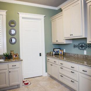 Bild på ett parallellt grovkök, med en undermonterad diskho, luckor med profilerade fronter, granitbänkskiva, gröna väggar, klinkergolv i keramik, en tvättmaskin och torktumlare bredvid varandra och vita skåp