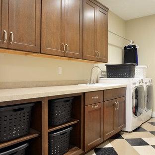 Exempel på en stor amerikansk linjär tvättstuga enbart för tvätt, med en nedsänkt diskho, skåp i shakerstil, laminatbänkskiva, beige väggar, linoleumgolv, en tvättmaskin och torktumlare bredvid varandra och skåp i mörkt trä