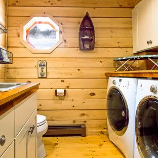 Idee per una piccola lavanderia multiuso american style con ante in stile shaker, ante beige, top in legno, lavatrice e asciugatrice affiancate, lavello da incasso, pareti marroni e parquet chiaro