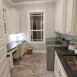 Cette image montre une grand buanderie parallèle craftsman dédiée avec un évier posé, un placard à porte shaker, des portes de placard blanches, un plan de travail en stéatite, un mur gris et un sol en bois brun.
