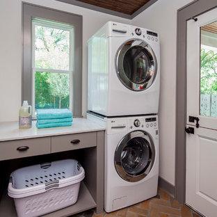 Klassisk inredning av en vita vitt tvättstuga enbart för tvätt, med släta luckor, grå skåp, bänkskiva i kvarts, vita väggar, en tvättpelare och tegelgolv