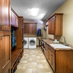 Inspiration för ett amerikanskt parallellt grovkök, med en nedsänkt diskho, luckor med infälld panel, skåp i mellenmörkt trä, laminatbänkskiva, beige väggar, linoleumgolv och en tvättmaskin och torktumlare bredvid varandra