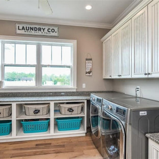 Large arts and crafts l-shaped utility room in Tampa with a single-bowl sink, beaded inset cabinets, white cabinets, granite benchtops, grey walls, medium hardwood floors, a side-by-side washer and dryer, multi-coloured floor and orange benchtop.