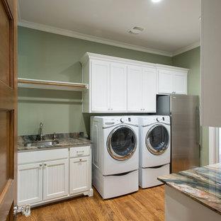 Idee per una grande lavanderia multiuso stile americano con lavello sottopiano, ante lisce, ante bianche, top in quarzite, pareti verdi, pavimento in legno massello medio e lavatrice e asciugatrice affiancate