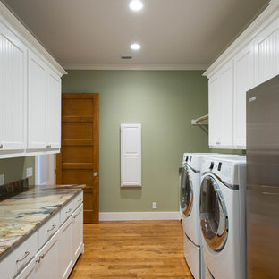 Foto di una grande lavanderia multiuso stile americano con lavello sottopiano, ante in stile shaker, ante bianche, top in quarzite, pareti verdi, pavimento in legno massello medio e lavatrice e asciugatrice affiancate