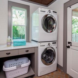 Idéer för mellanstora amerikanska l-formade tvättstugor, med skåp i shakerstil, bruna skåp, bänkskiva i kvarts, vita väggar, tegelgolv, en tvättpelare och orange golv