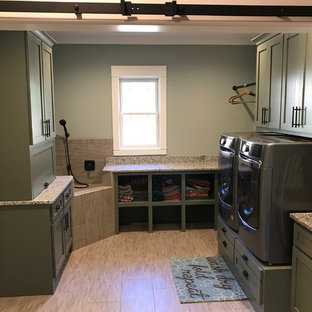 Mid-sized transitional u-shaped dedicated laundry room in Raleigh with shaker cabinets, grey cabinets, granite benchtops, grey walls, vinyl floors, a side-by-side washer and dryer and beige floor.