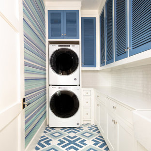 Laundry room - transitional l-shaped multicolored floor and wallpaper laundry room idea in Dallas with a farmhouse sink, louvered cabinets, blue cabinets, multicolored walls, a stacked washer/dryer and white countertops