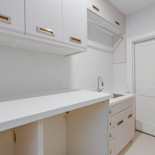 Design ideas for a small modern single-wall utility room in Toronto with an undermount sink, flat-panel cabinets, stainless steel cabinets, quartz benchtops, white walls, porcelain floors, a side-by-side washer and dryer, white floor and white benchtop.