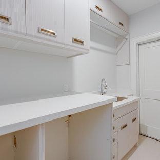Foto på ett litet funkis vit linjärt grovkök, med en undermonterad diskho, släta luckor, skåp i rostfritt stål, bänkskiva i kvarts, vita väggar, klinkergolv i porslin, en tvättmaskin och torktumlare bredvid varandra och vitt golv