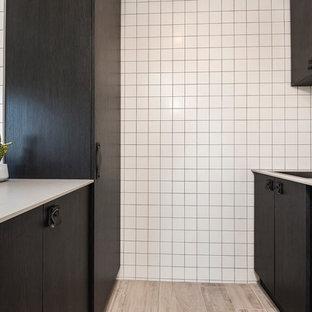 Foto på en mellanstor nordisk grå parallell tvättstuga enbart för tvätt, med en enkel diskho, släta luckor, svarta skåp, bänkskiva i kvarts, vitt stänkskydd och klinkergolv i keramik