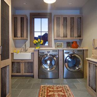 Foto di una grande sala lavanderia tradizionale con lavello stile country, ante con riquadro incassato, top in quarzo composito, pareti beige, pavimento in ardesia, lavatrice e asciugatrice affiancate e ante in legno bruno