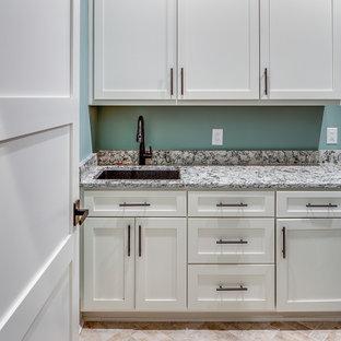 Rustik inredning av en mellanstor flerfärgade linjär flerfärgat tvättstuga enbart för tvätt, med en undermonterad diskho, skåp i shakerstil, vita skåp, blå väggar och beiget golv