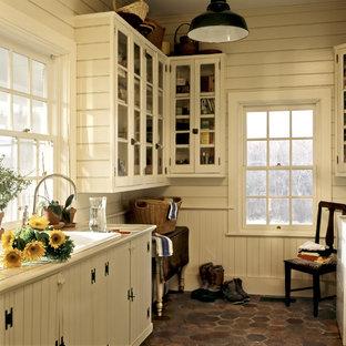 Exemple d'une buanderie nature multi-usage avec un évier posé, un placard à porte vitrée, des portes de placard blanches, un plan de travail en carrelage, un mur blanc et des machines côte à côte.