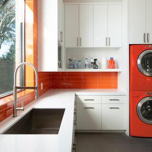 Ispirazione per una grande sala lavanderia minimal con lavello sottopiano, ante lisce, ante bianche, lavatrice e asciugatrice a colonna, pavimento grigio, top bianco e paraspruzzi arancione