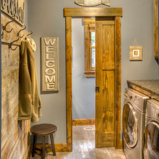 Design ideas for a rustic single-wall utility room in Minneapolis with grey walls, a side by side washer and dryer, brown floors and black worktops.