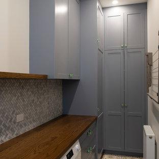 Idéer för en stor medelhavsstil linjär tvättstuga enbart för tvätt, med en nedsänkt diskho, skåp i shakerstil, grå skåp, träbänkskiva, vita väggar, klinkergolv i keramik, en tvättmaskin och torktumlare bredvid varandra och gult golv