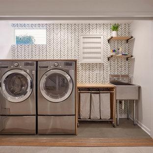 Foto på en mellanstor vintage linjär liten tvättstuga, med en allbänk, träbänkskiva, betonggolv, en tvättmaskin och torktumlare bredvid varandra, grönt golv och vita väggar