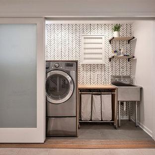 Ispirazione per un ripostiglio-lavanderia classico di medie dimensioni con lavatoio, top in legno, pavimento in cemento, lavatrice e asciugatrice affiancate, pavimento verde e pareti grigie