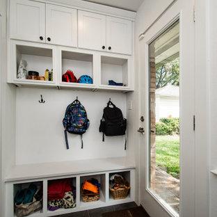 Idéer för mellanstora linjära vitt grovkök, med en enkel diskho, släta luckor, vita skåp, bänkskiva i kvarts, vita väggar, klinkergolv i porslin, en tvättpelare och grått golv
