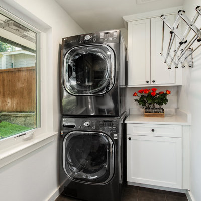 Mid-sized transitional single-wall porcelain tile and gray floor dedicated laundry room photo in Dallas with white cabinets, quartz countertops, white walls, a stacked washer/dryer, white countertops and shaker cabinets