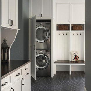 Utility room - beach style black floor utility room idea in Minneapolis with shaker cabinets, white cabinets, wood countertops, gray walls and a stacked washer/dryer