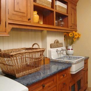 Idéer för en mellanstor amerikansk grå linjär tvättstuga enbart för tvätt, med en rustik diskho, luckor med upphöjd panel, skåp i mellenmörkt trä, laminatbänkskiva, beige väggar, klinkergolv i terrakotta, en tvättmaskin och torktumlare bredvid varandra och rött golv