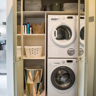 Imagen de armario lavadero lineal, bohemio, pequeño, con armarios abiertos, paredes blancas, suelo de cemento, lavadora y secadora apiladas, suelo blanco y encimeras blancas
