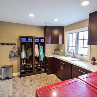 Inspiration for a large traditional u-shaped utility room in Chicago with an utility sink, shaker cabinets, dark wood cabinets, granite worktops, brown walls, porcelain flooring, a side by side washer and dryer and beige floors.