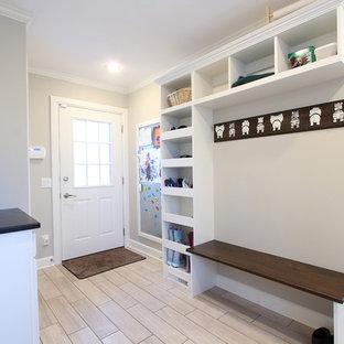 Idéer för mellanstora vintage u-formade grovkök, med en enkel diskho, släta luckor, vita skåp, bänkskiva i täljsten, grå väggar, kalkstensgolv och en tvättpelare