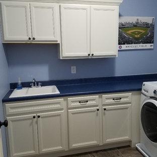 Exempel på en mellanstor blå l-formad blått tvättstuga enbart för tvätt, med en nedsänkt diskho, luckor med infälld panel, vita skåp, laminatbänkskiva, blå väggar, klinkergolv i keramik, en tvättmaskin och torktumlare bredvid varandra och brunt golv