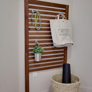 Exempel på en liten modern linjär tvättstuga enbart för tvätt, med beige väggar, klinkergolv i porslin och en tvättpelare
