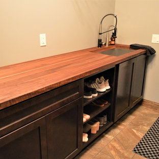 Design ideas for a small country single-wall dedicated laundry room in Other with an undermount sink, shaker cabinets, dark wood cabinets, wood benchtops, beige walls, ceramic floors, a stacked washer and dryer, beige floor and brown benchtop.