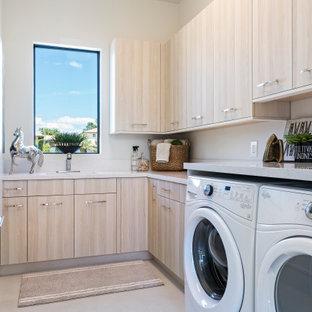 Exempel på en modern grå l-formad grått tvättstuga enbart för tvätt, med en undermonterad diskho, släta luckor, bruna skåp, vita väggar, en tvättmaskin och torktumlare bredvid varandra och beiget golv